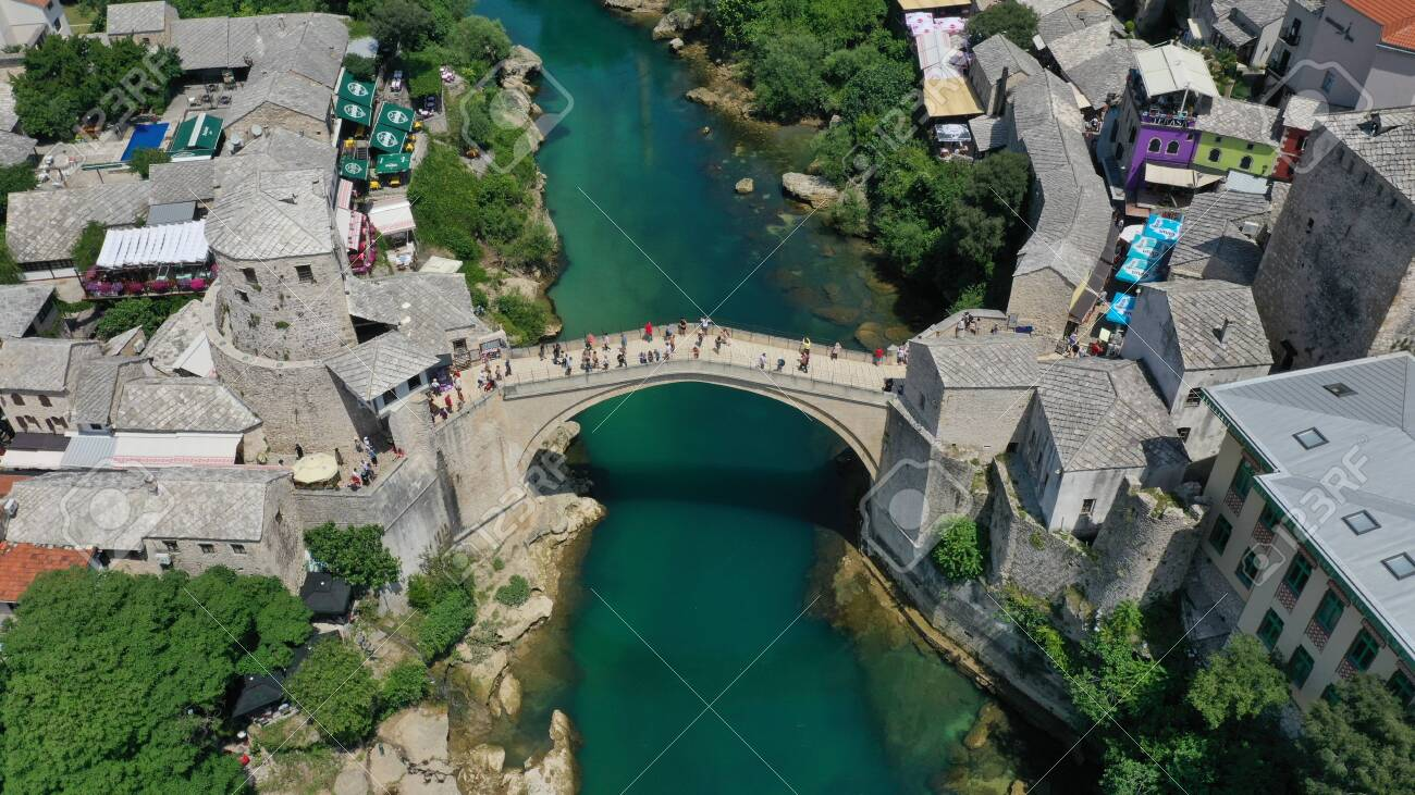 Aerial view of Stari Most old medieval bridge in Mostar, Neretva river, Bosnia and Herzegovina. Tourists walking on the bridge. Summer landscape of old town. Mosque on background. - 139967243