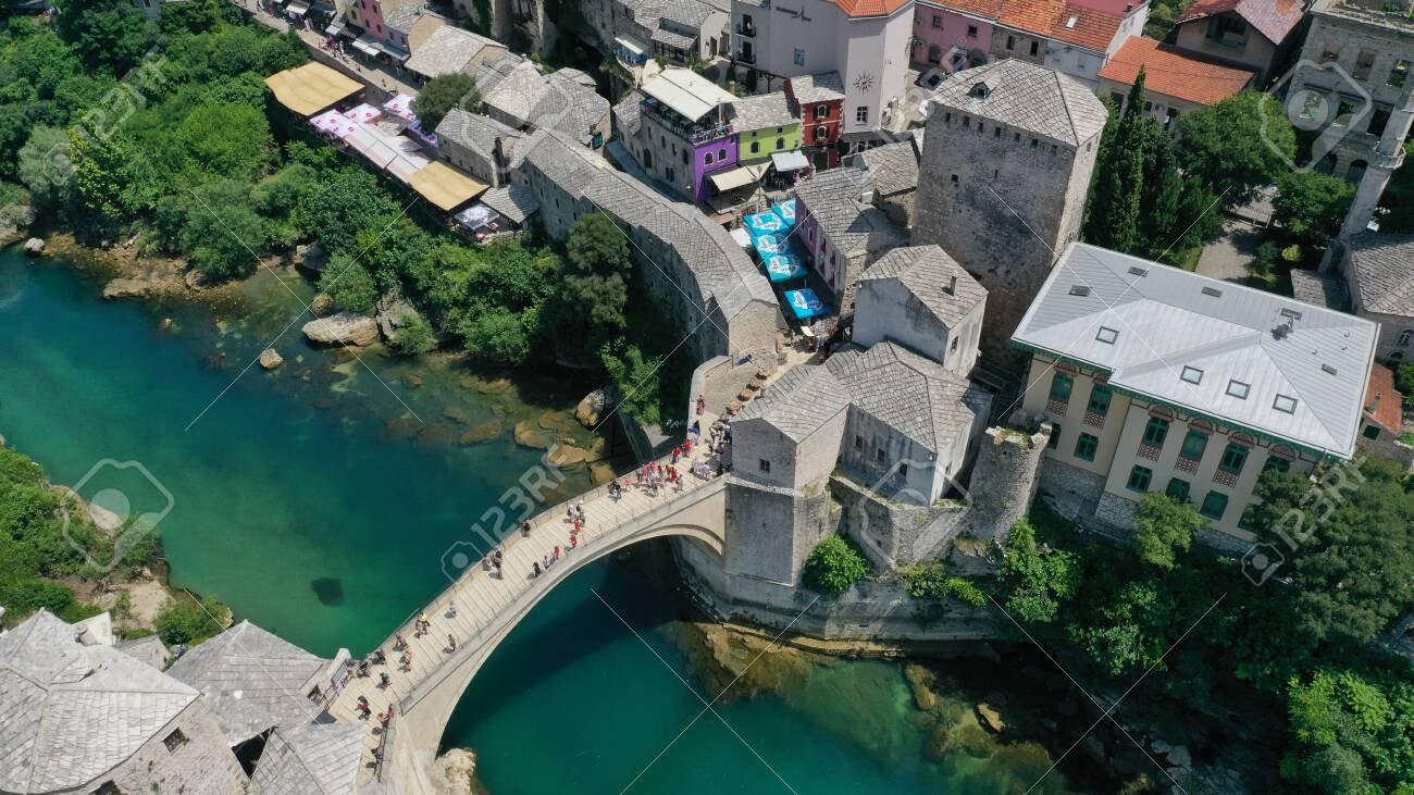 Aerial view of Stari Most old medieval bridge in Mostar, Neretva river, Bosnia and Herzegovina. Tourists walking on the bridge. Summer landscape of old town. Mosque on background. - 139967249