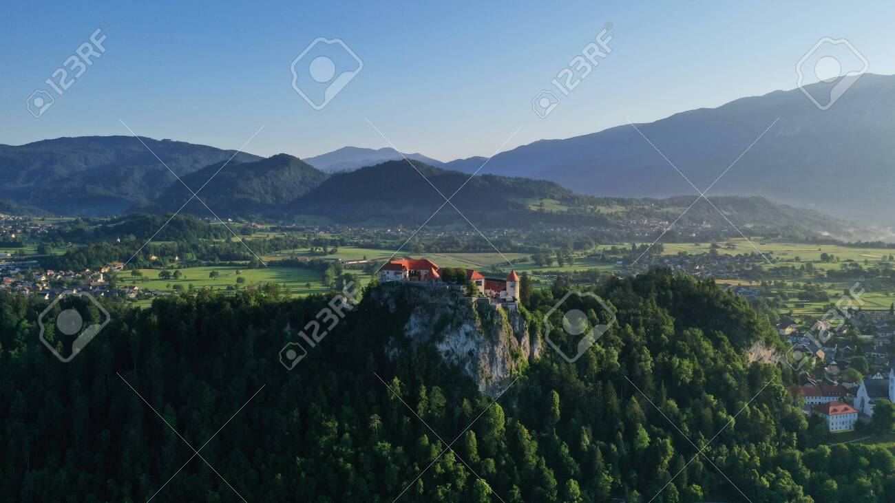 Aerial footage of Bled castle on rocky cliff, Lake Bled in Slovenia, Europe. Natural mountainous landscape around castle, green meadows and fields. Summer. - 139967956