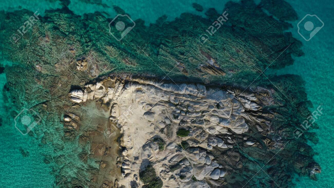 Aerial view of Vourvourou beach, small peninsula in turquoise water of Aegean sea. Waves beating cliff rocky coastline. Halkidiki, Greece. - 140592820