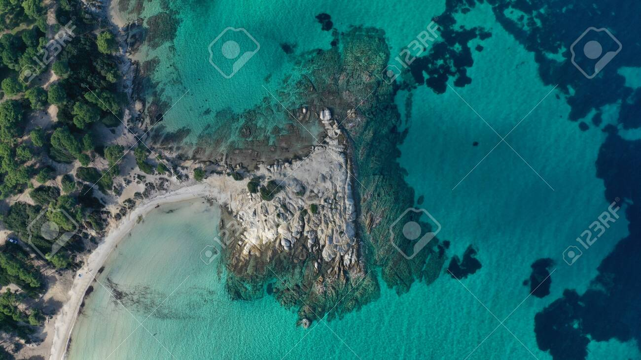Aerial view of Vourvourou beach, small peninsula in turquoise water of Aegean sea. Waves beating cliff rocky coastline. Halkidiki, Greece. - 140592862