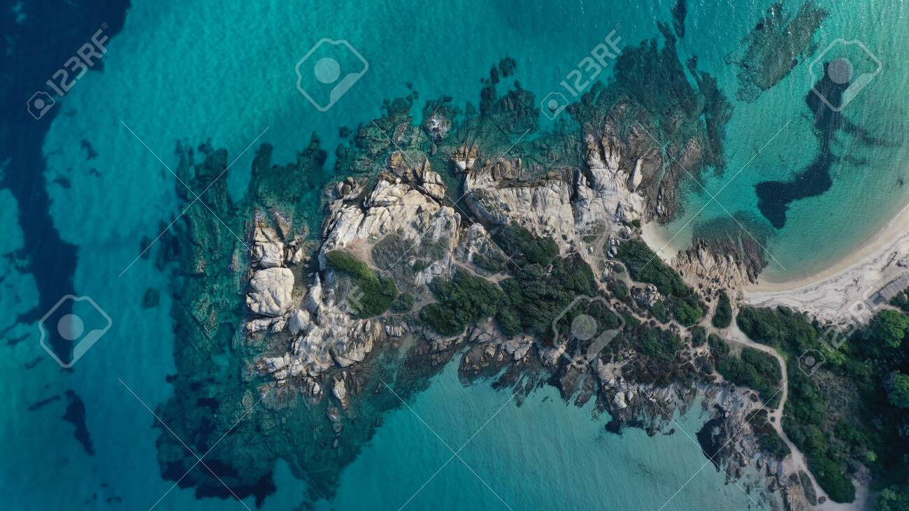 Aerial view of Vourvourou beach, small peninsula in turquoise water of Aegean sea. Waves beating cliff rocky coastline. Halkidiki, Greece. - 140592865