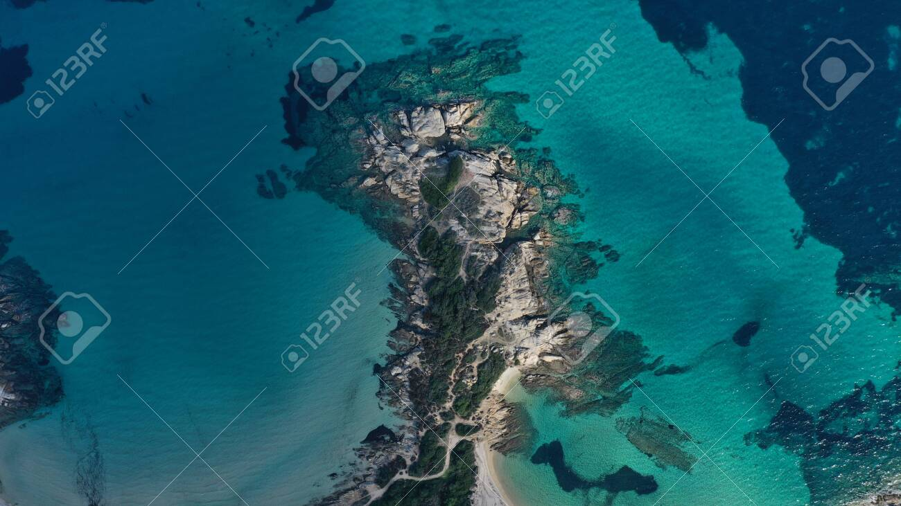 Aerial view of Vourvourou beach, small peninsula in turquoise water of Aegean sea. Waves beating cliff rocky coastline. Halkidiki, Greece. - 140592866