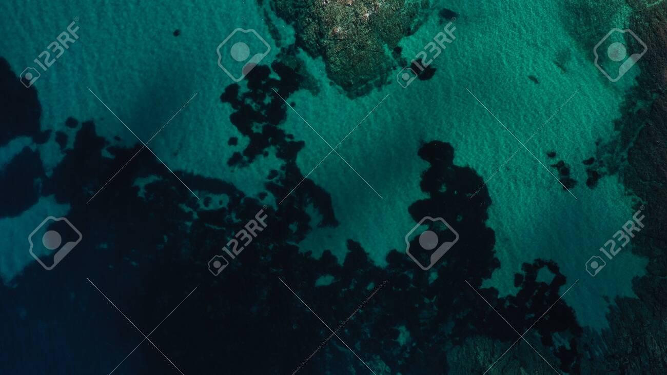 Aerial view of Aegean sea, turquoise water surface, Vourvourou beach, Kavourotripes beach, Sithonia peninsula, Halkidiki, Greece. Rocks, stones underwater. - 140592867