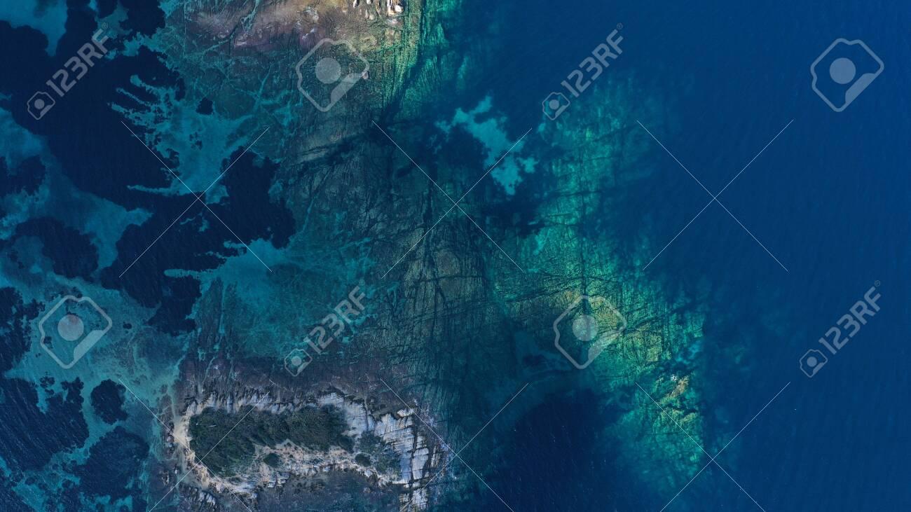 Aerial view of Aegean sea, turquoise water surface, Vourvourou beach, Kavourotripes beach, Sithonia peninsula, Halkidiki, Greece. Rocks, stones underwater. - 140592869
