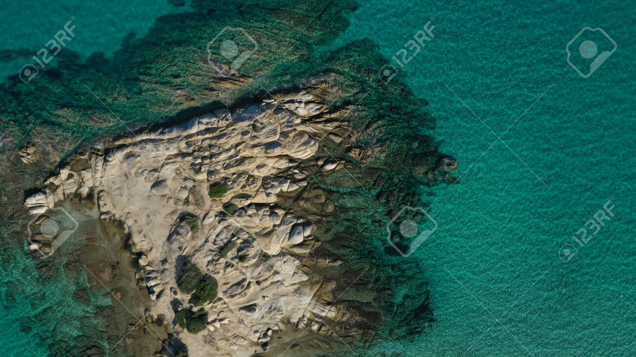 Aerial view of Vourvourou beach, small peninsula in turquoise water of Aegean sea. Waves beating cliff rocky coastline. Halkidiki, Greece. - 143387880