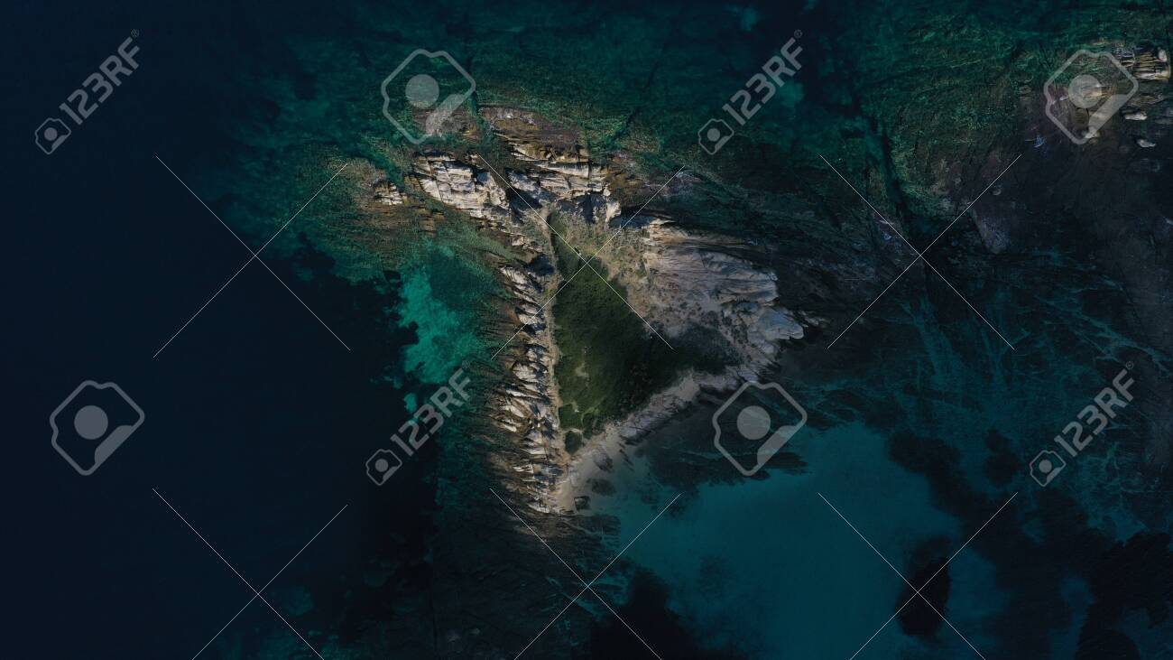 Aerial top down view of small island, islet in turquoise water of Aegean sea. Vourvourou beach, Halkidiki, Greece. - 143387876