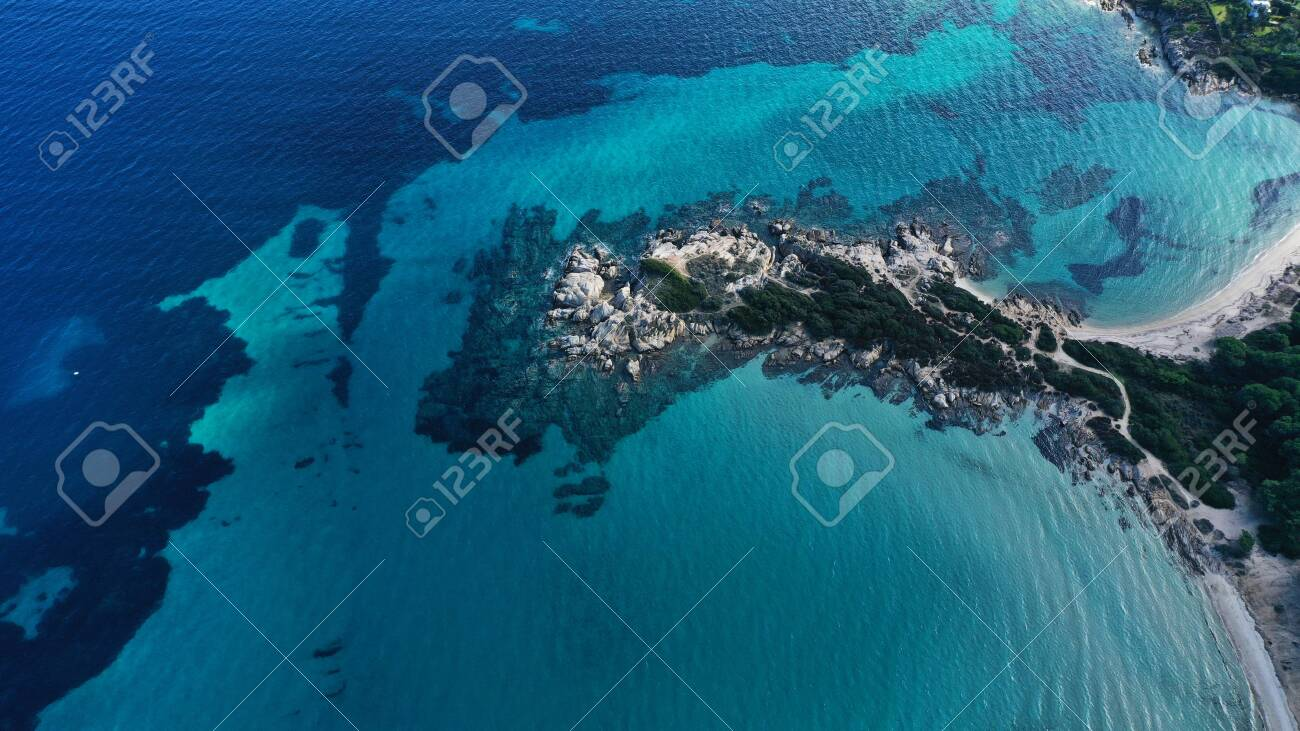 Aerial view of Vourvourou beach, small peninsula in turquoise water of Aegean sea. Waves beating cliff rocky coastline. Halkidiki, Greece. - 143387884