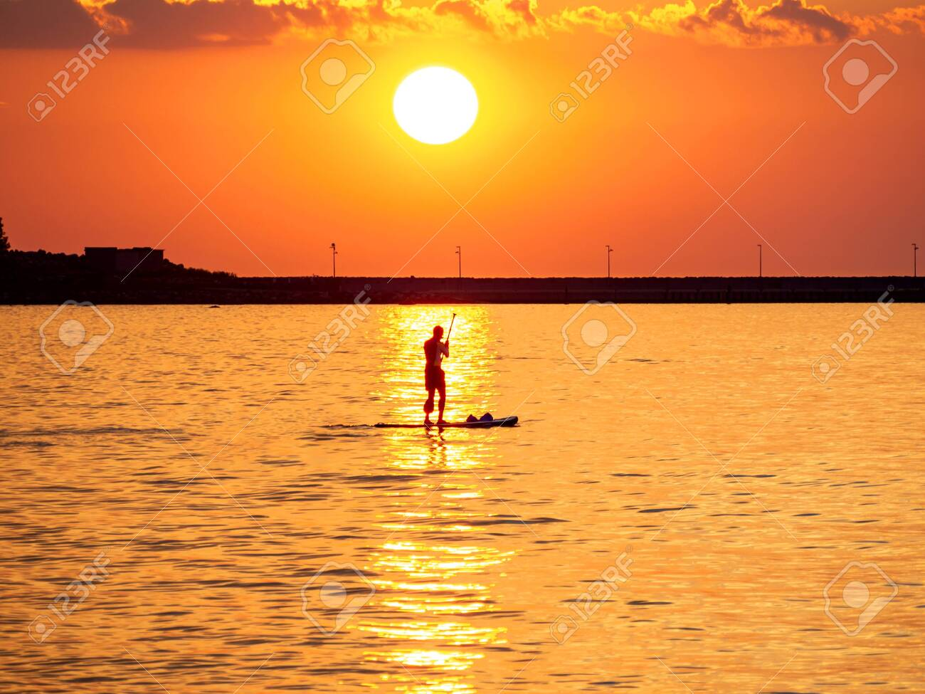 Sunset Silhouette Of Summer Surfing Man Standing On Paddle Board
