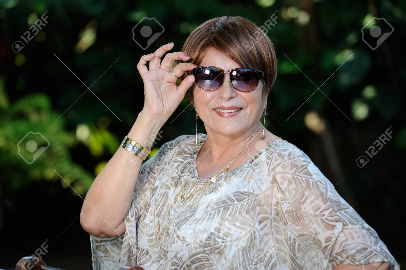 0a1b924d8f smiling old lady hold sunglasses on summer park Stock Photo - 53171978