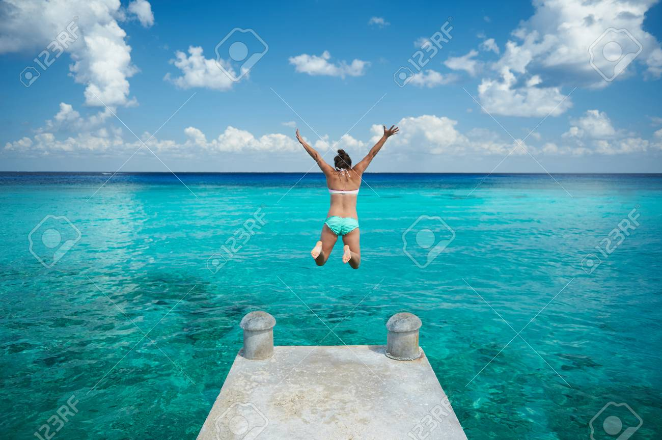 One woman jump in blue water from pier view from back on caribbean vacation - 70794146