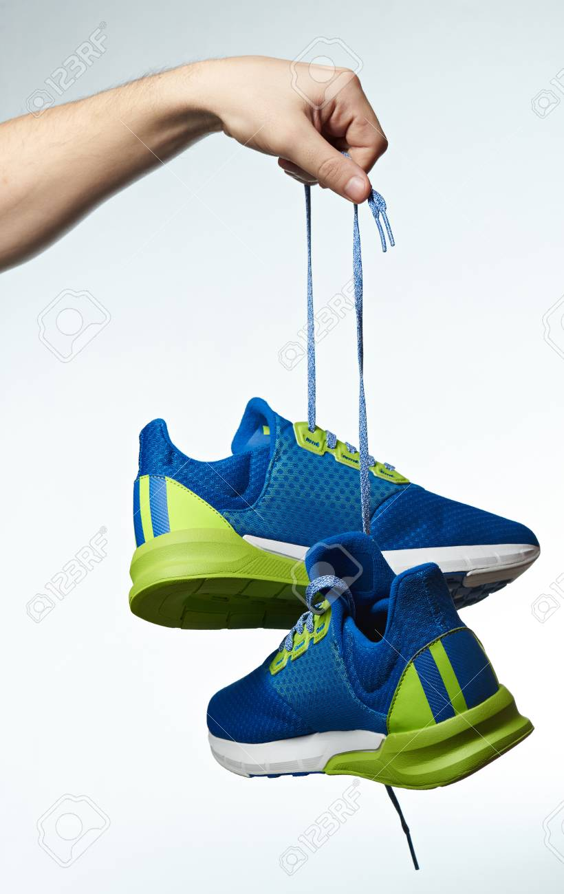 Hand holding colorful running shoes isolated on white background