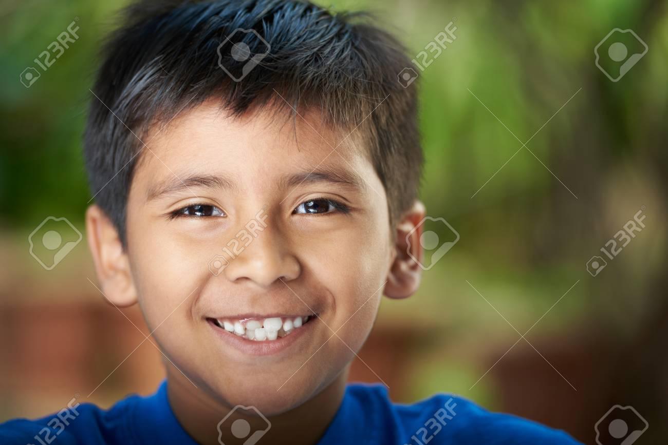 Close-up portrait of boy smiling with teeth. Hispanic boy headshot - 83813493