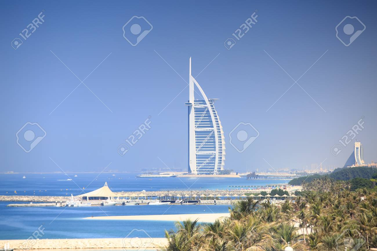 Luxury seven stars hotel in Dubai. Burj Al Arab Jumeirah resort hotel on blue sky background. Sunny Dubai resort. - 89511906