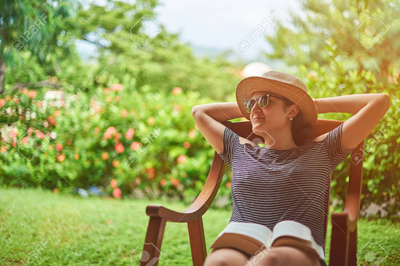 Summer vacation concept. Young woman sitting in backyard - 91180178