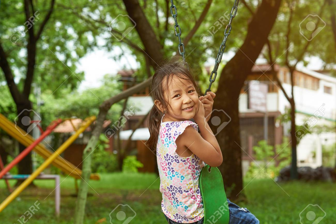 Cheerful asian small girl sitting in park swings Stock Photo - 103841425