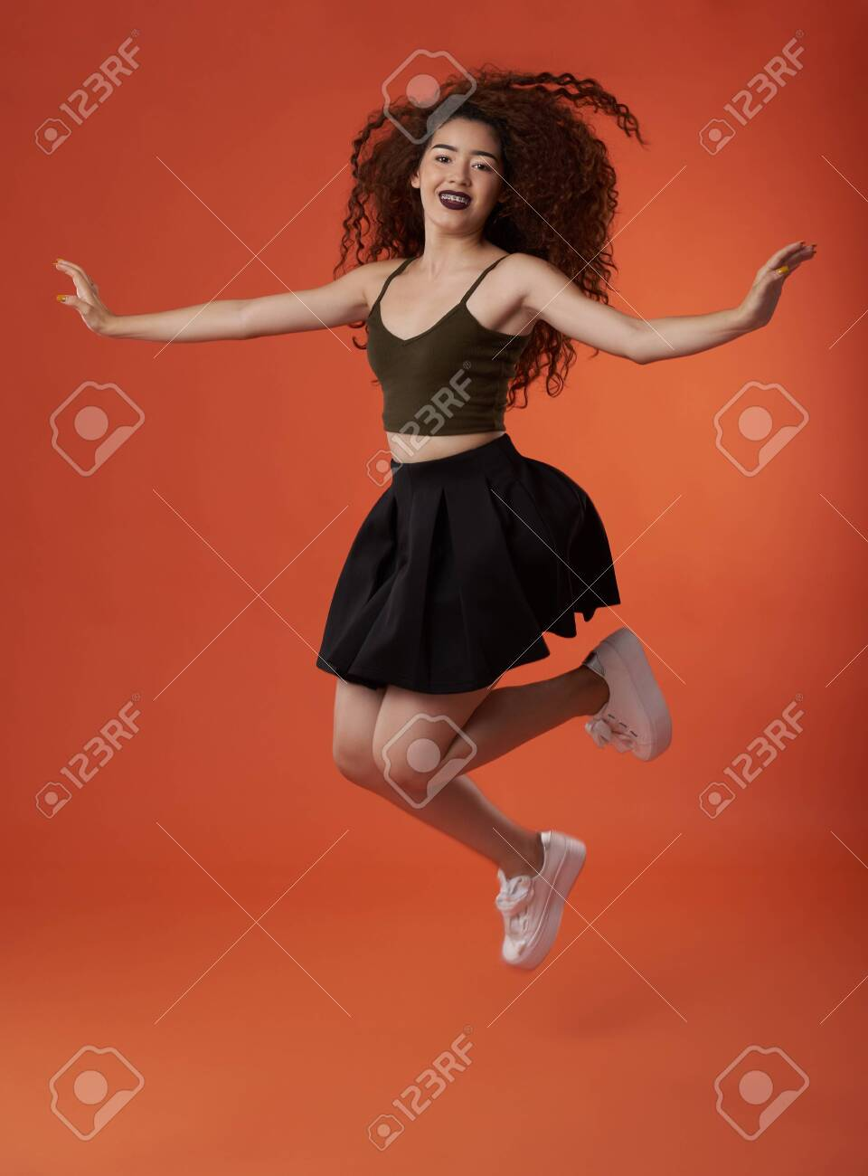 Jumping happy young brunette woman with curly hair - 128284889