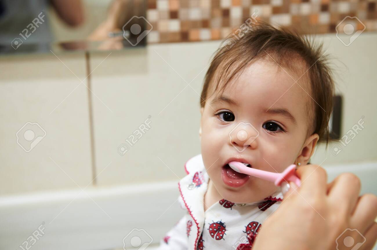 Brushing kid teeth theme. Portrait of baby girl with toothbrush in mouth - 135201011