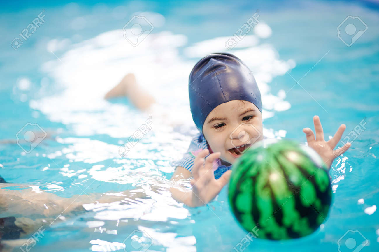 Kid catching ball in blue water pool. Swimming exercise at school - 171896497