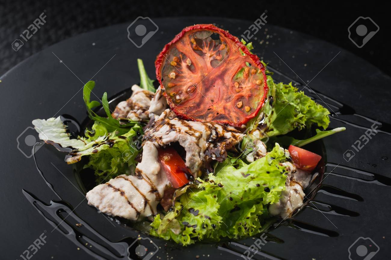 Tasty Salad With Veal And Tomato In Black Plate On Dark Table Stock Photo Picture And Royalty Free Image Image 90879324