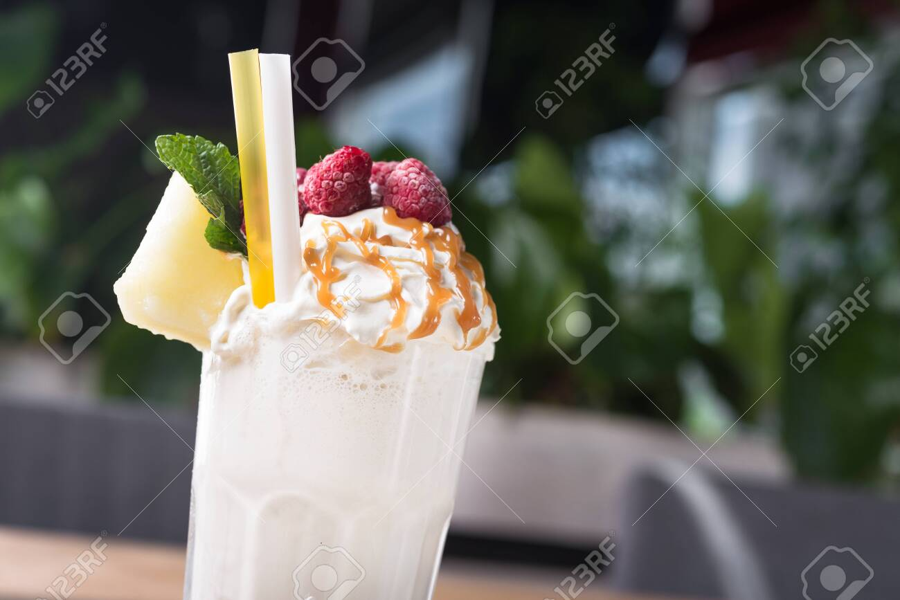 Closeup of tasty summer milk shakes with melon slice and caramel topping on a cafe table. - 129596795