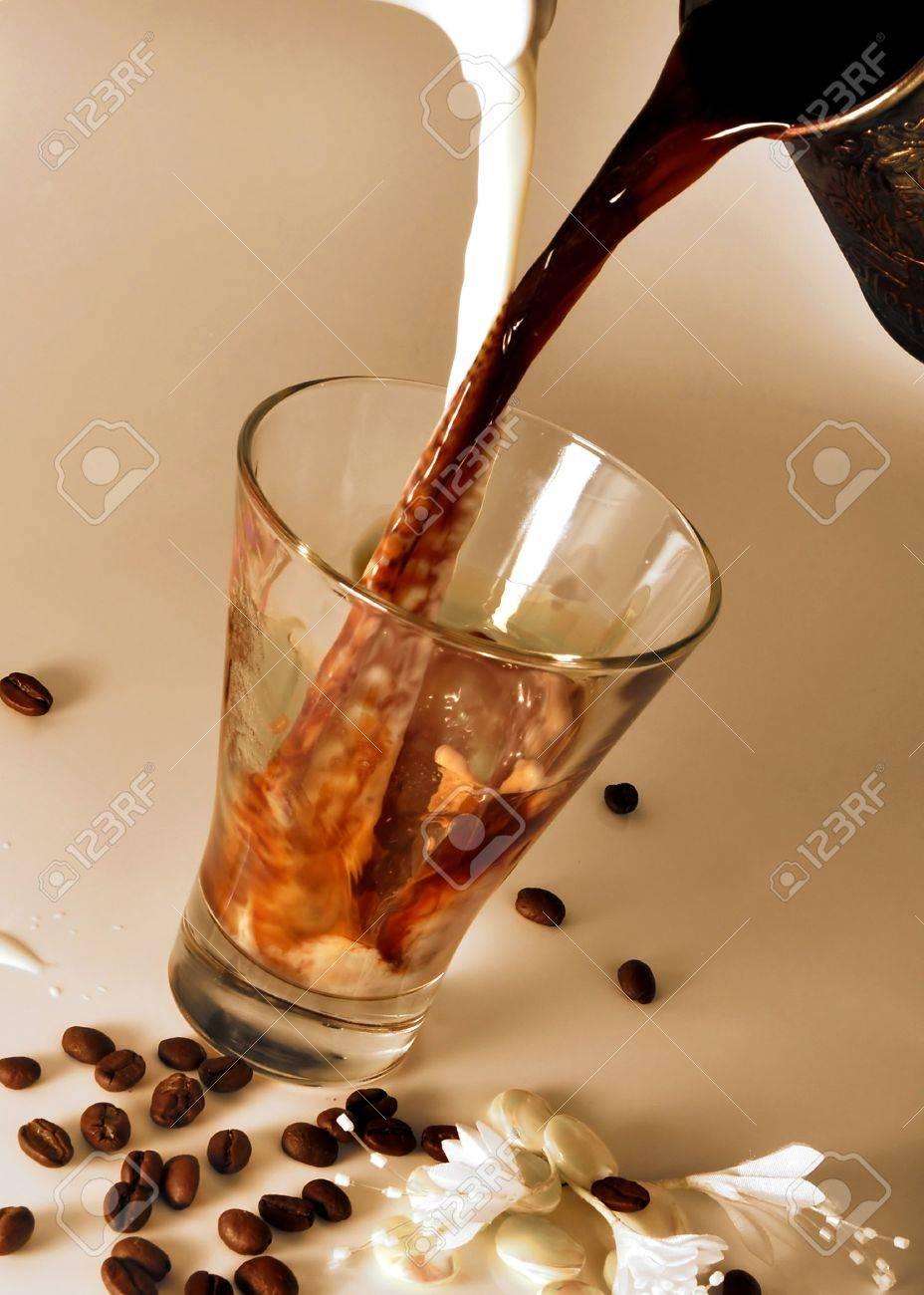 kaffee und milch ausgießen in einem transparenten glas und mischen