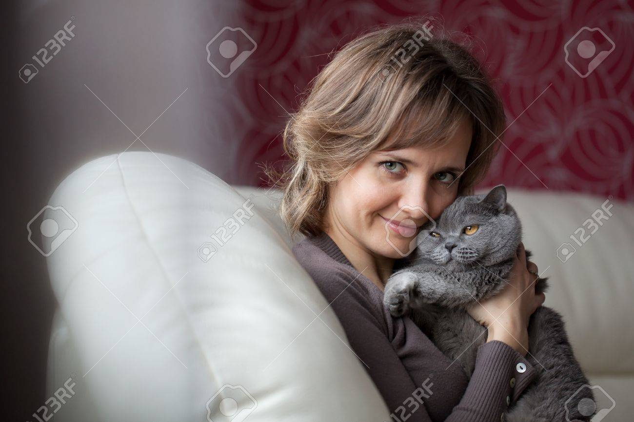 Young woman sitting on the couch and fondles gray cat Stock Photo - 12043829