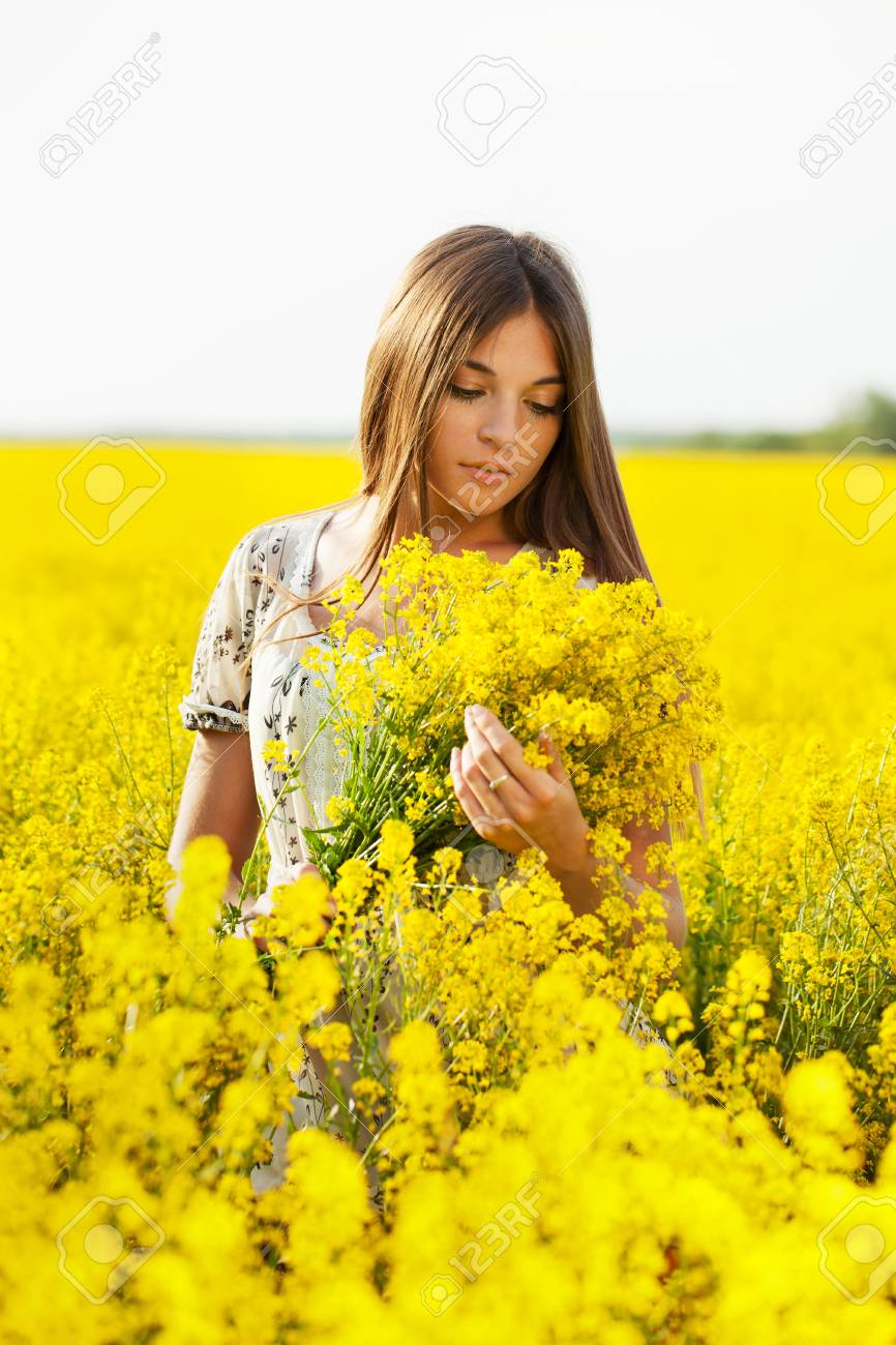Girl With Long Hair Holding A Bouquet Of Yellow Flowers Stock Photo