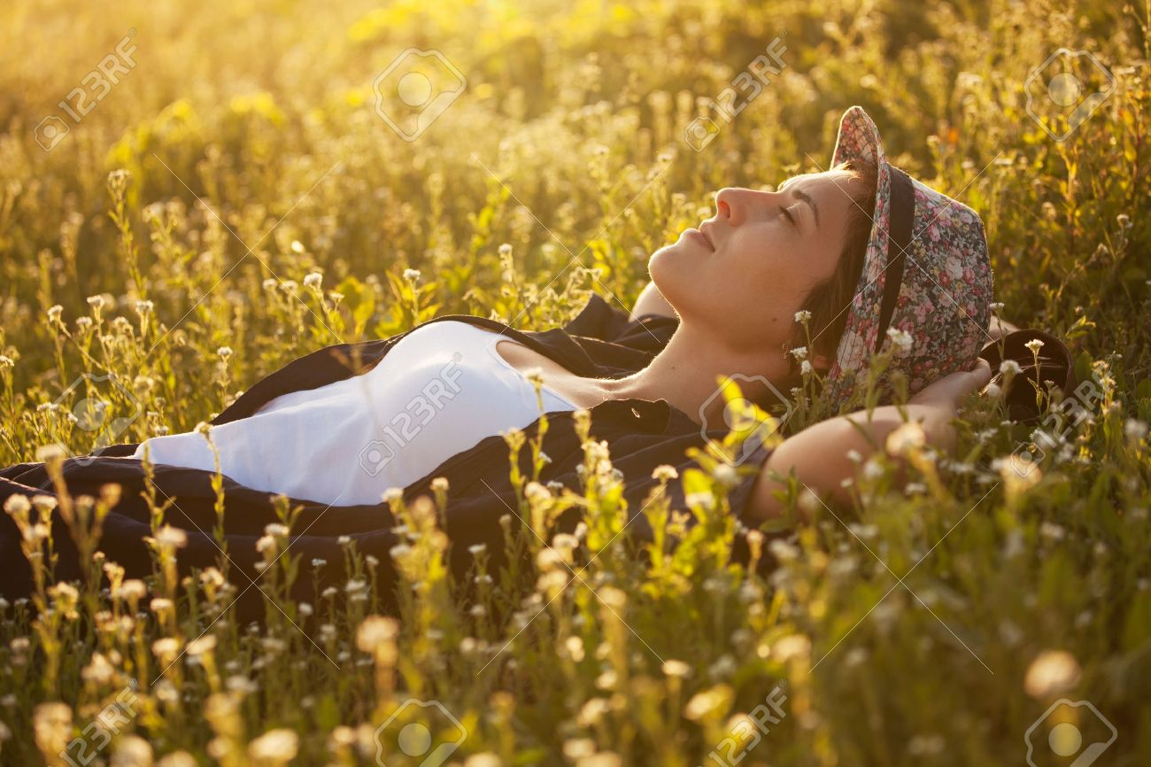 The girl in a hat dremet among wildflowers at sunset Stock Photo - 20593862