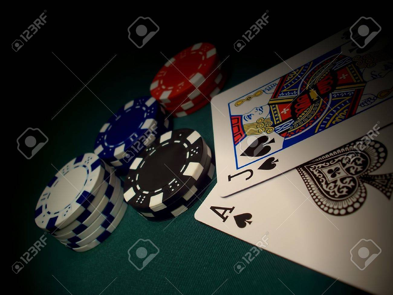 Red, Blue, White, Black Poker Chips On A Green Felt Gaming Table.