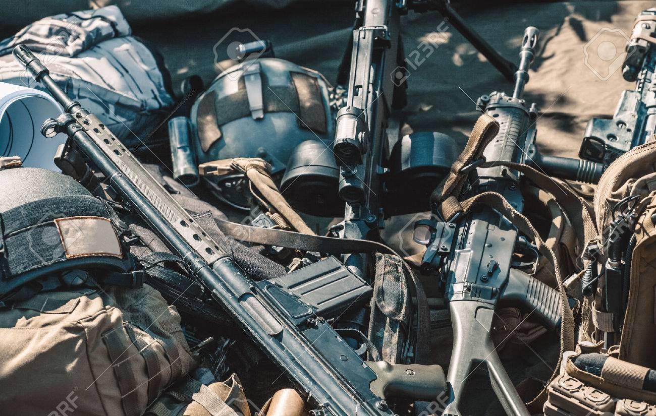 automatic machine, machine gun, helmet, body armor piled in a heap lie on the ground. - 62665816