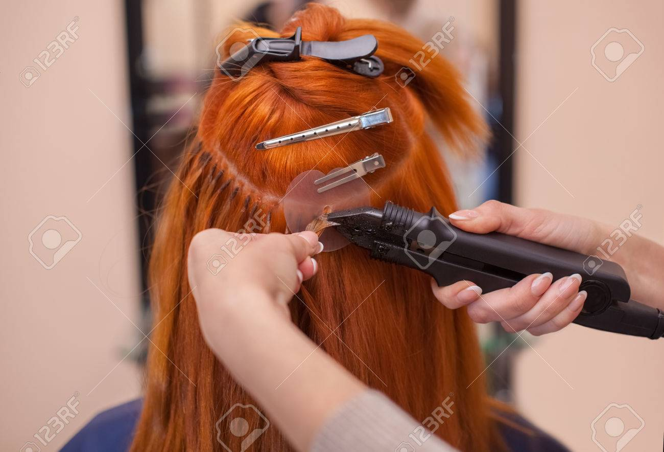 The hairdresser does hair extensions to a young red haired girl the hairdresser does hair extensions to a young red haired girl in a pmusecretfo Image collections
