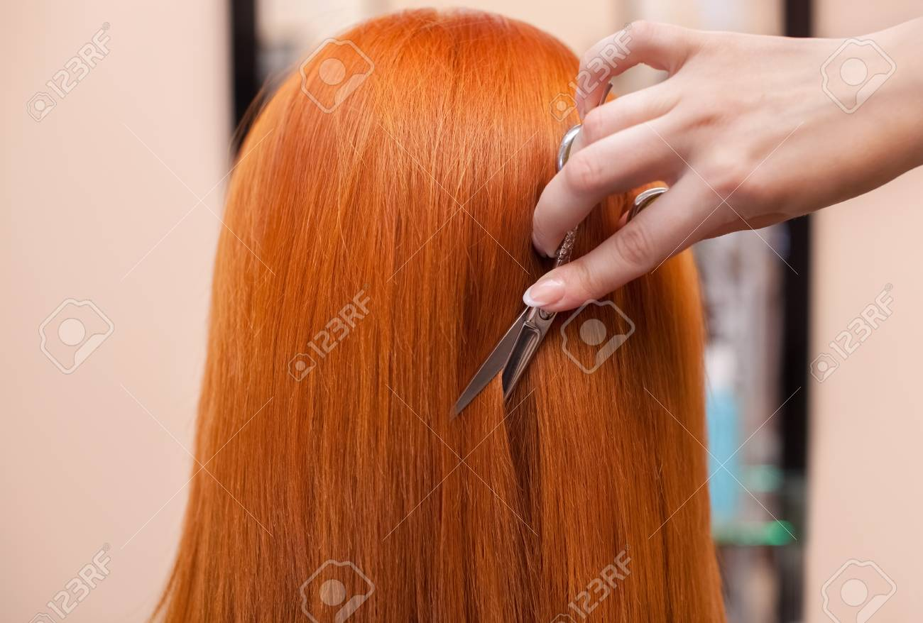 The Hairdresser Does A Haircut With Scissors Of Hair To A Young