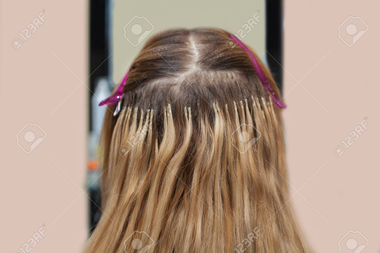 The Hairdresser Does Hair Extensions To A Young Girl A Blonde