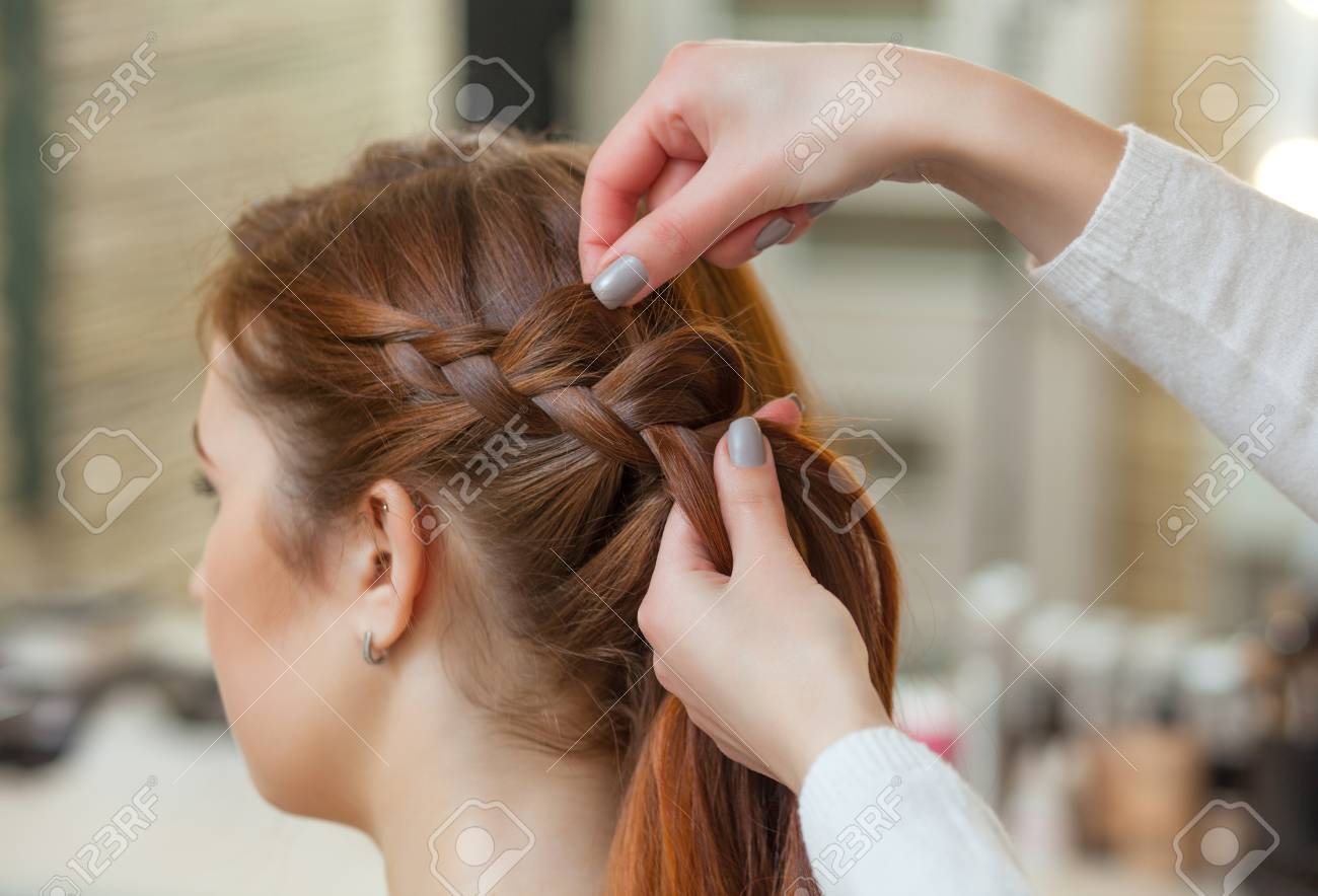 Beautiful Girl With Long Red Hair Hairdresser Weaves A Braid