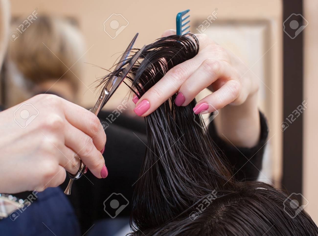 The Hairdresser Does A Haircut With Hot Scissors Of Hair To A