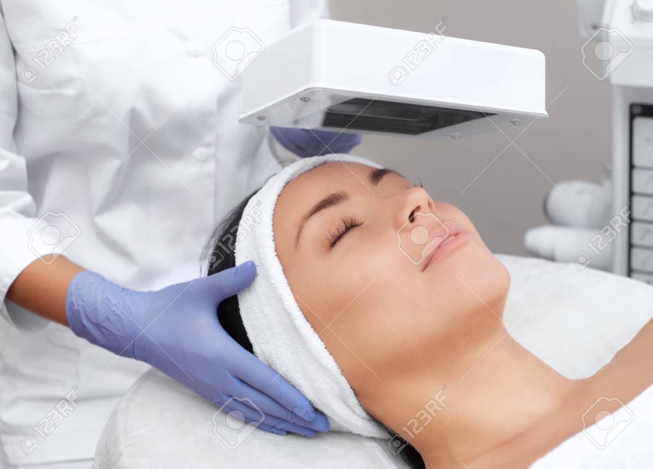 The cosmetologist uses the Wood Lamp for detailed diagnosis of the skin condition. The device detects the presence of skin diseases or inflamed areas. Cosmetology and professional care. - 102697566