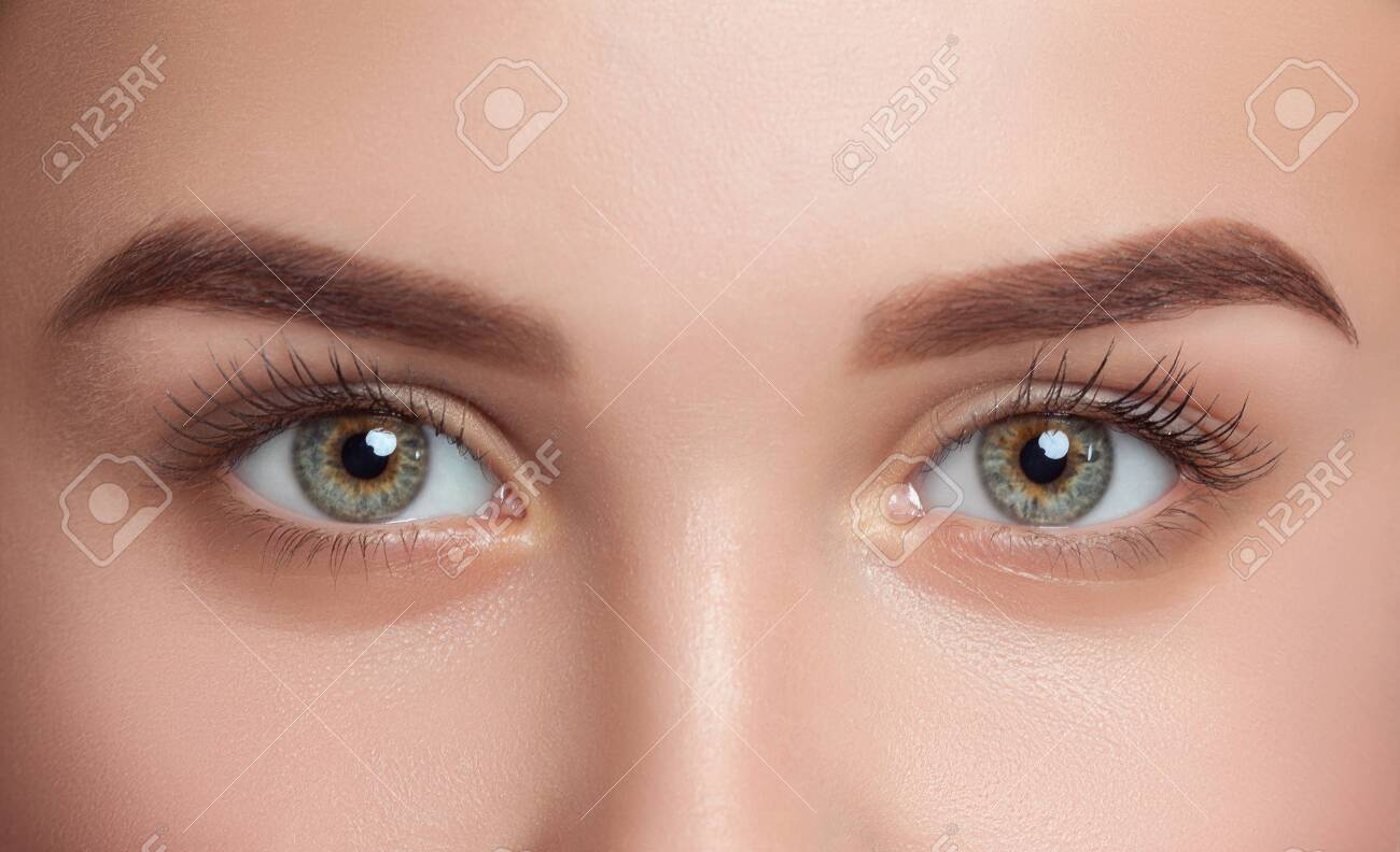 Beautiful woman with long eyelashes, beautiful make-up and thick eyebrows. Beautiful blue eyes close up. Looking at the camera. Professional makeup and cosmetology skin care. - 141105291