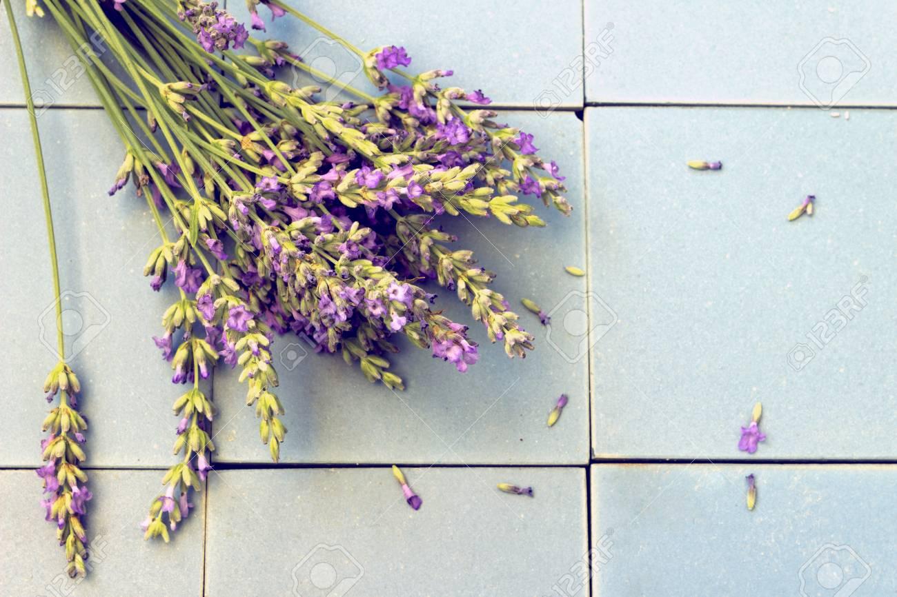 261ed8453 Foto de archivo - Un ramo de flores de lavanda en azulejos de cerámica  azules. Estilo retro