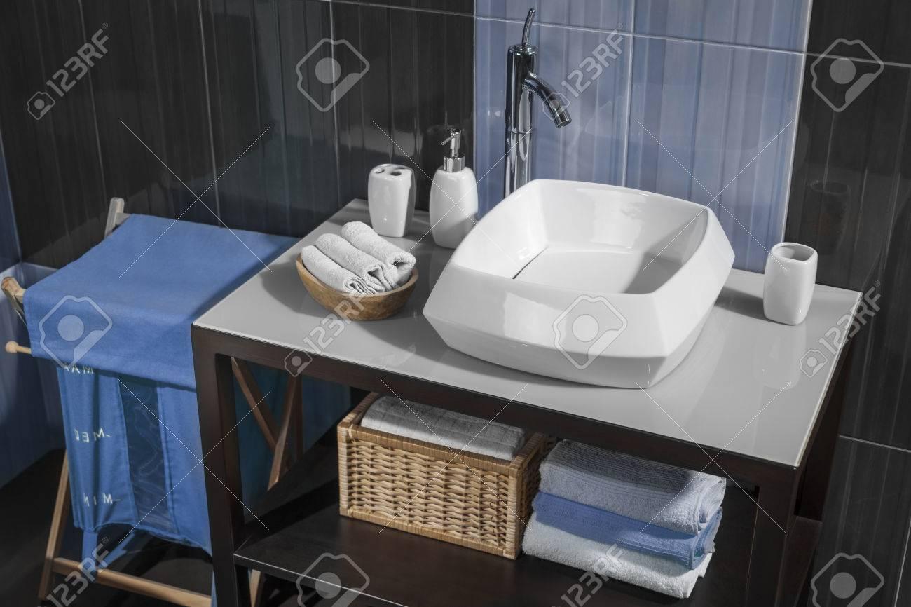 Detalle de un moderno cuarto de baño con lavabo y accesorios de baño  gabinete y los azulejos del baño azul