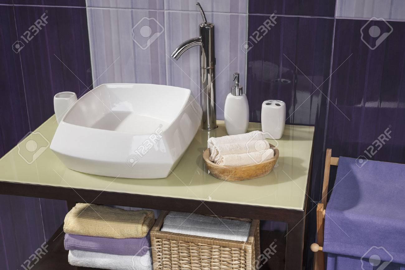 Detalle de un moderno cuarto de baño con lavabo y accesorios de baño  gabinete y los azulejos del baño de color púrpura