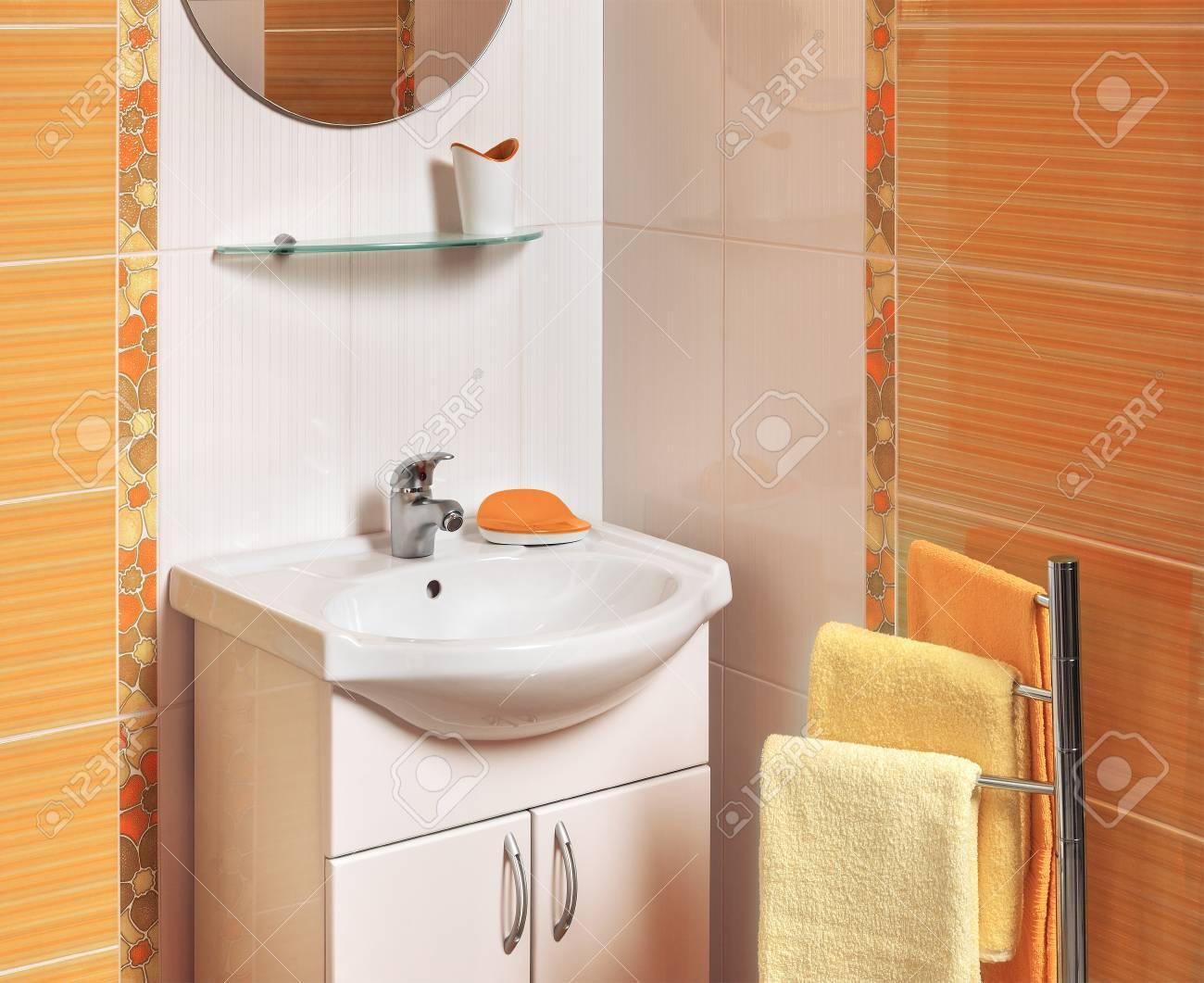 Détail d\'une salle de bains luxueuse avec des accessoires avec des carreaux  orange et blanc