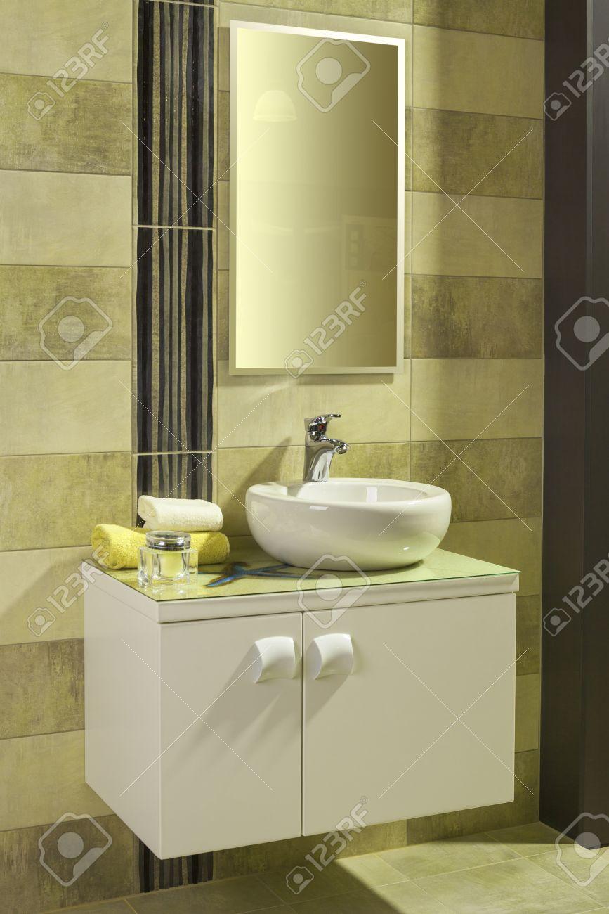 Rund vit handfat i ett modernt badrum med gula och grå plattor ...