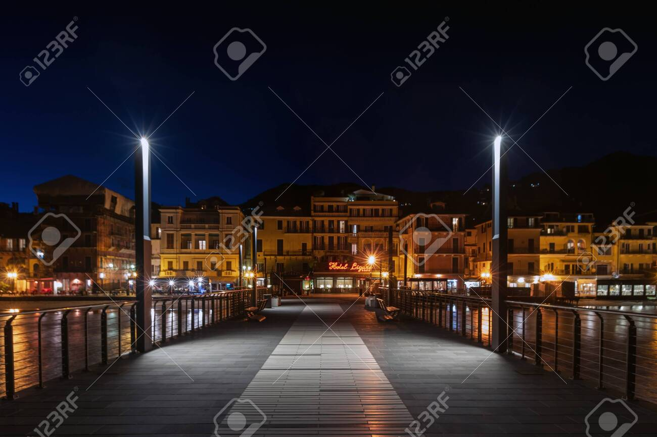 Alassio, Italy - February 26, 2020: View of Alassio from a pier in the night - 142975977