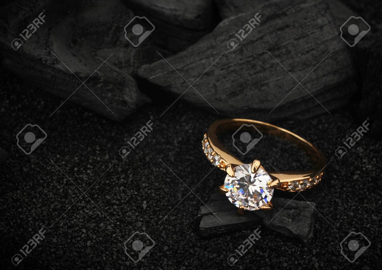 jewelry ring witht big diamond on dark coal and black sand background - 56026098