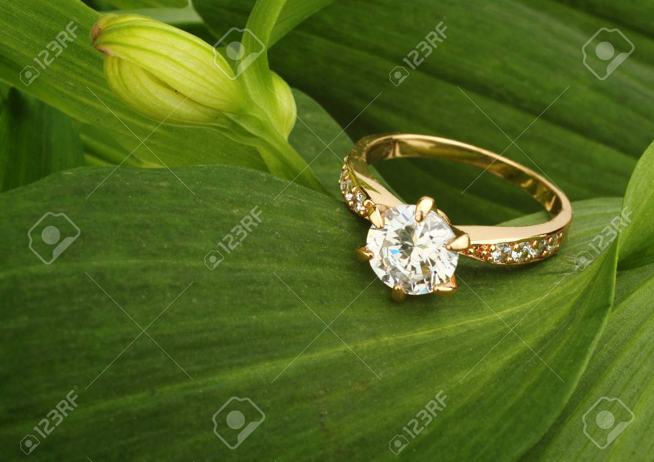 Jewellry ring with big diamond on green leafs background - 69322438