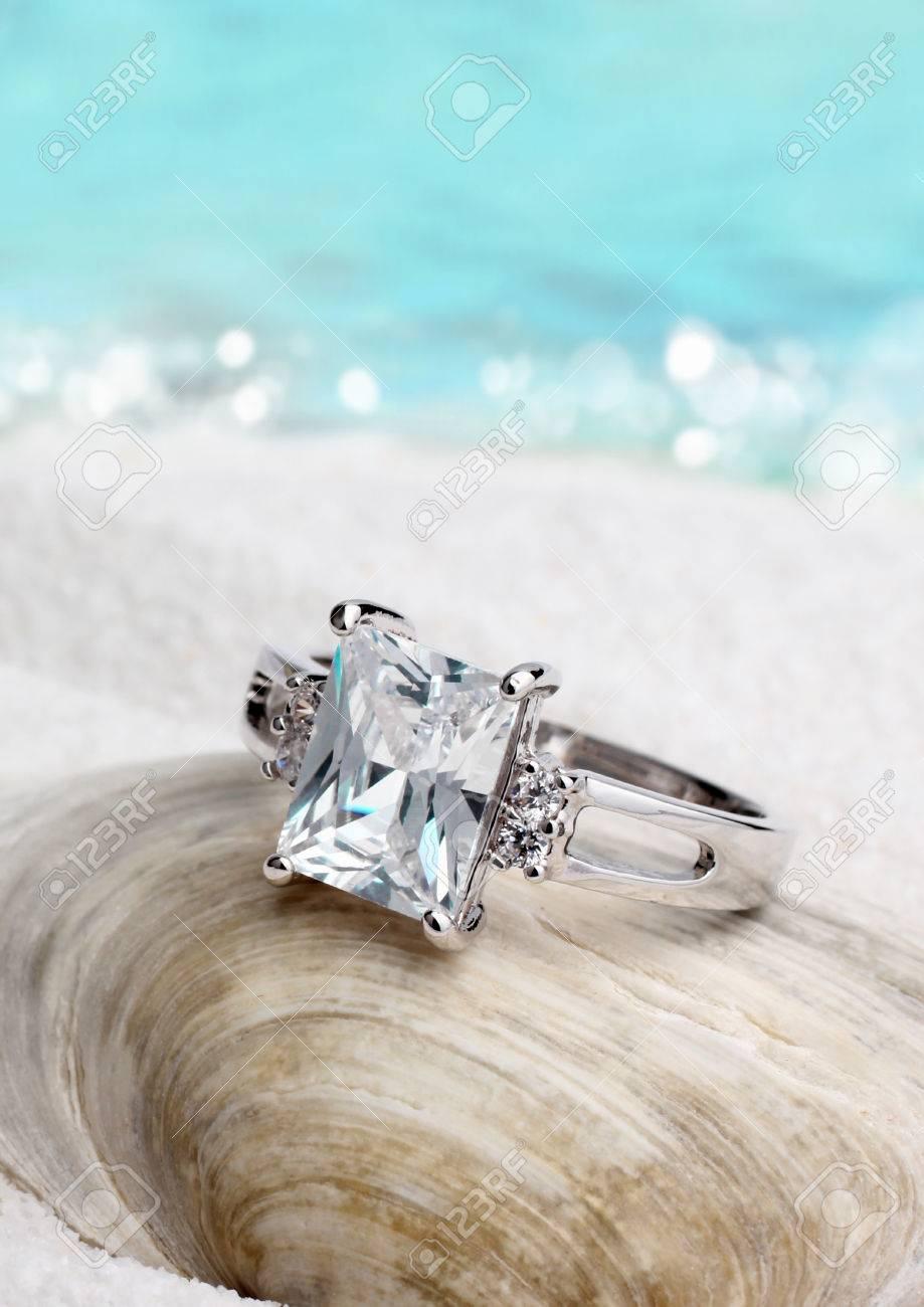917e66360d52 Foto de archivo - Joyería anillo con diamante en la playa de arena de  fondo