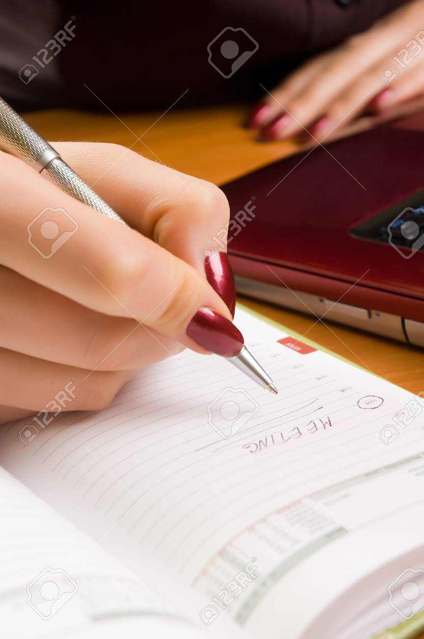 Young woman at desk writing a note (shallow dof). Stock Photo - 4521374