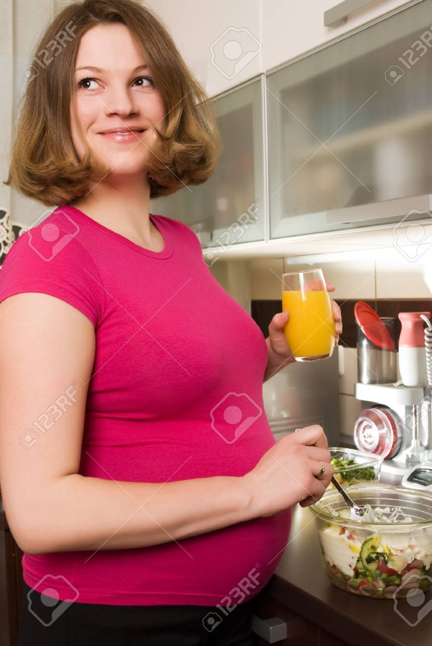 Young pregnant woman in kitchen making a salad and smiling Stock Photo - 4855134