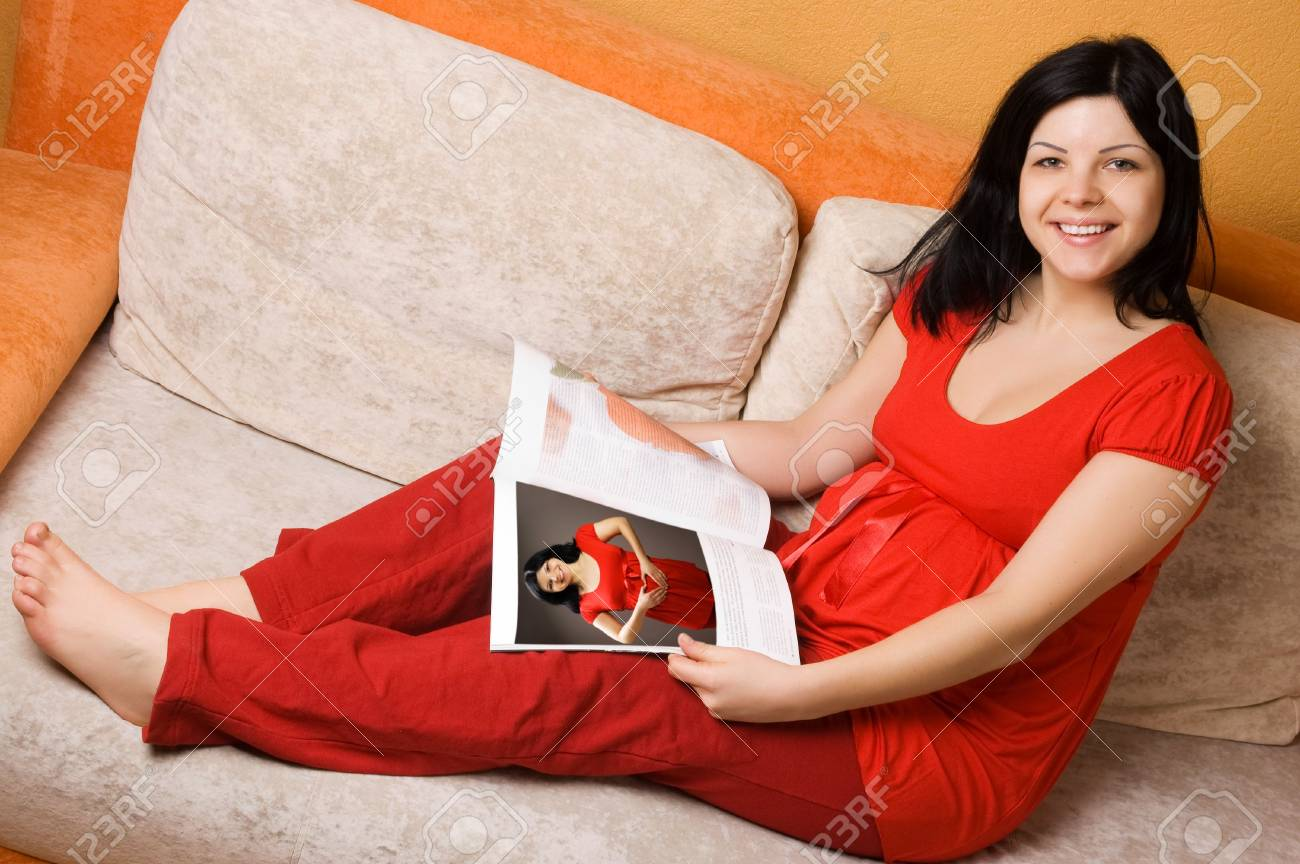 Beautiful pregnant woman sitting on the couch Stock Photo - 5908643